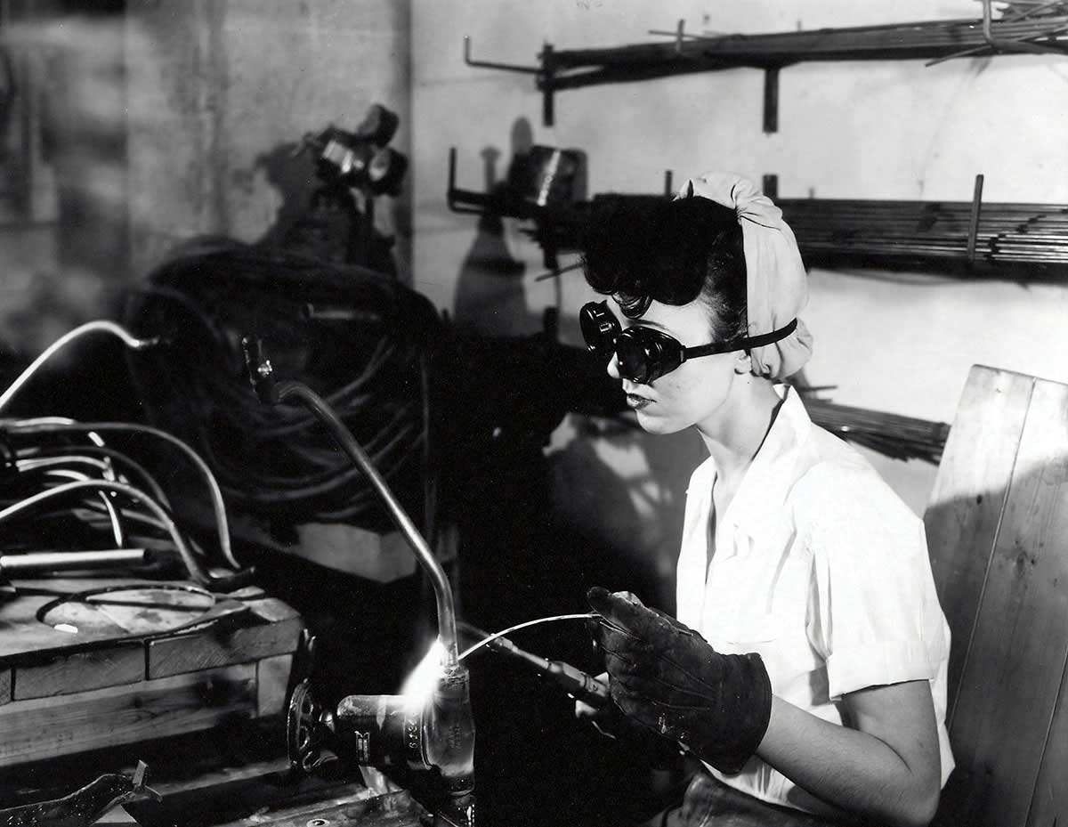 Black and white photo of a woman in WW2 welding.
